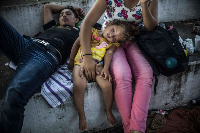 """TOPSHOT - Honduran migrants taking part in a caravan heading to the US, rest during a stop in their journey, in Huixtla, Chiapas state, Mexico, on October 23, 2018. - Thousands of mainly Honduran migrants heading to the United States -- a caravan President Donald Trump has called an """"assault on our country"""" -- stopped to rest Tuesday after walking for two days into Mexican territory. (Photo by PEDRO PARDO / AFP)        (Photo credit should read PEDRO PARDO/AFP/Getty Images)"""
