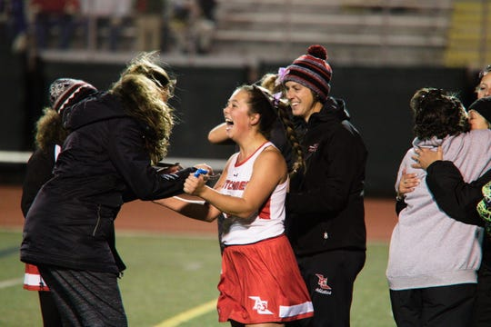 Annville-Cleona's Elizabeth Matusiak, center, is congratulated by her coaches after her goal with no time left in OT lifted A-C to a dramatic 2-1 win over Bishop McDevitt in a District 3 1A first round playoff game at Milton Hershey Wednesday night.