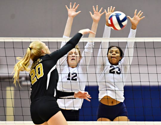 Delone Catholic's Brooke Lawyer, left, hits the ball across the net while West York's Kirsten Bowser, center, and Alayna Harris defend during York-Adams League girls' volleyball championship action at Dallastown Area High School in York Township, Wednesday, Oct. 24, 2018. West York would win the title game 3-0. Dawn J. Sagert photo