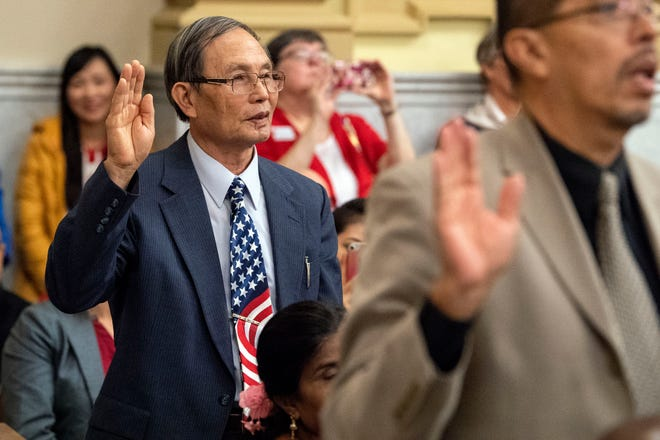 Mien Dinh Nguyen of York, who came to the United States from Vietnam, takes the Oath of Allegiance during a naturalization ceremony at the York County Administration Center on Thursday. Nguyen was one of two students who completed the York County Literacy Council's English as a Second Language program. The 49 new citizens who were naturalized Thursday immigrated from 30 different countries.