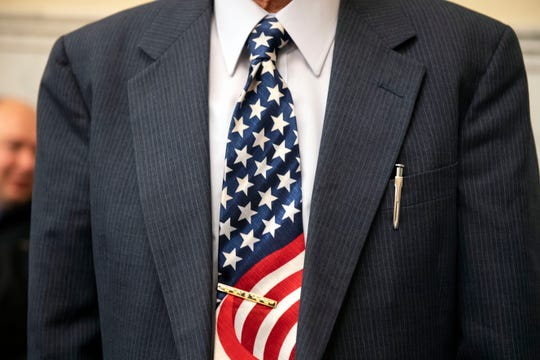 Mien Dinh Nguyen, originally from Vietnam, shows off his American flag themed tie during a naturalization ceremony at the York County Administration Center on Thursday.