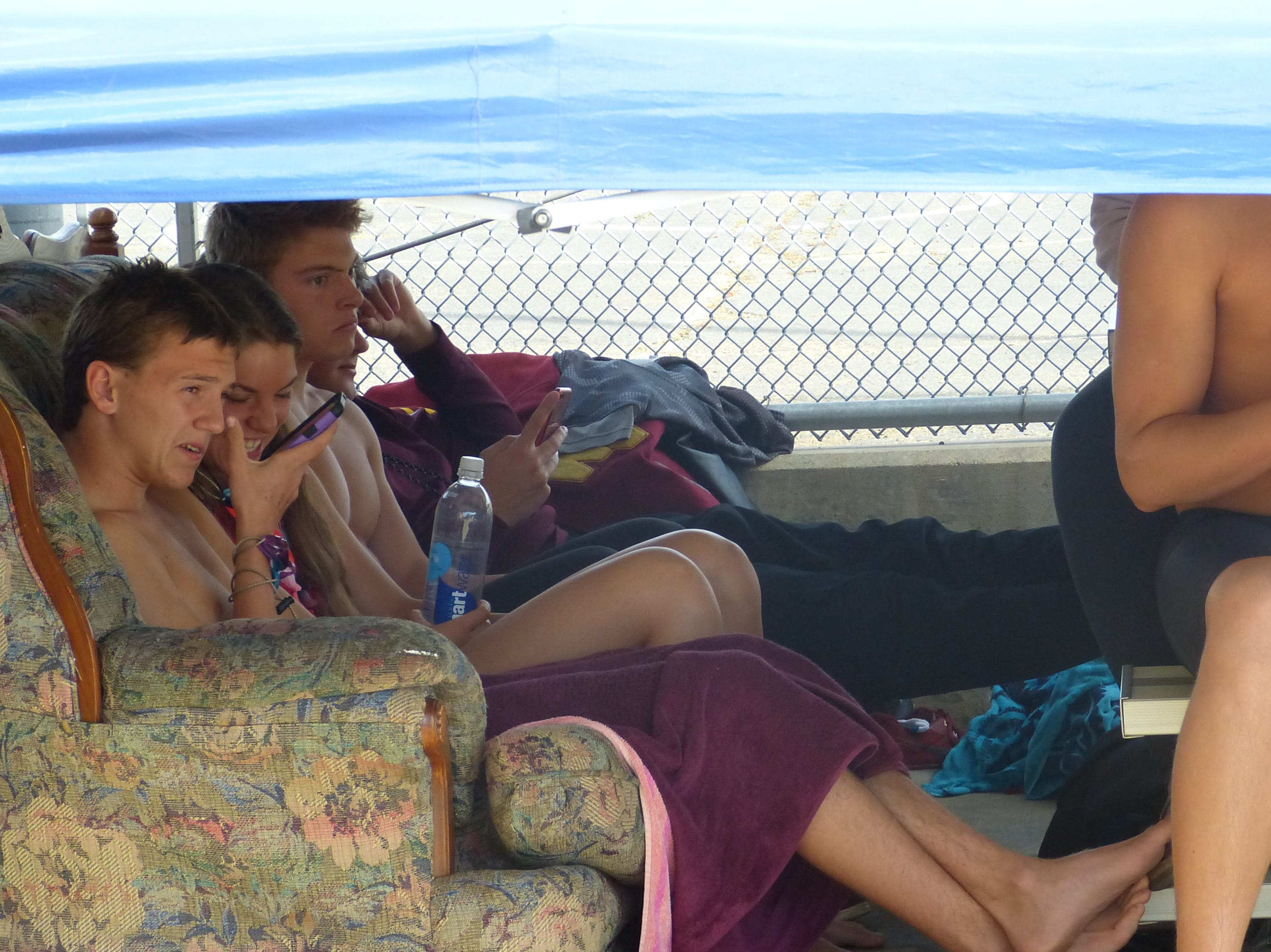 West Valley swimmers hang out on a couch under their tent between events Wednesday at the NSCIF trials for Division 2 schools at West Valley High School on Oct. 24, 2018.
