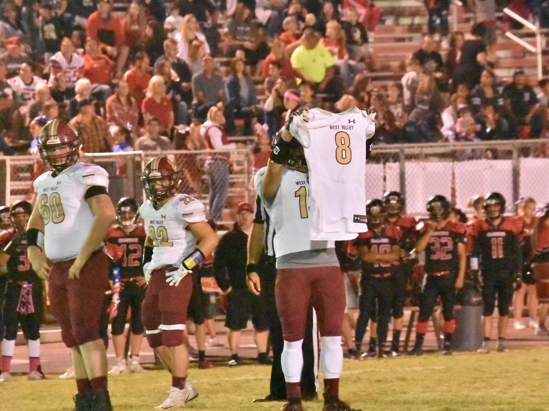 West Valley's Bailey Sulzer holds up Tyson Wacker's jersey before the Eagles' first defensive play of the game. Wacker, a junior defensive end, was injured in a vehicle crash on Oct. 18  died as a result of his injuries the following Monday.