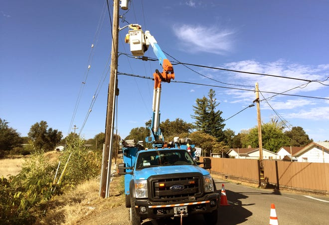 Pacific Gas & Electric troubleman Calem Colgate upgrades a streetlight along 1st Street in Cottonwood on Thursday. The utility installed 36 new streetlights to about double the light output to improve safety at the request of Shasta County officials. Cottonwood residents have been on the lookout for whoever's been setting fires around the town.
