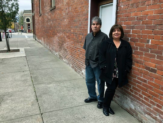 In this Oct. 23, 2018 photo, Delmiro Trevino and his wife Oralia pose in front of a building in Independence, where the Hi-Ho restaurant used to be located. It was in that restaurant, in 1977, that Delmiro Trevino was in when three sheriff's deputies and a policewoman came in and demanded he show documents proving he was American. The racial profiling of Trevino, an American born in Texas, led to Oregon becoming America's first sanctuary state. Now, Oregonians are deciding in the Nov. 6 election whether to repeal the law, even as some other states, like Vermont, have adopted sanctuary policies and others, like Texas, have banned towns from adopting them.