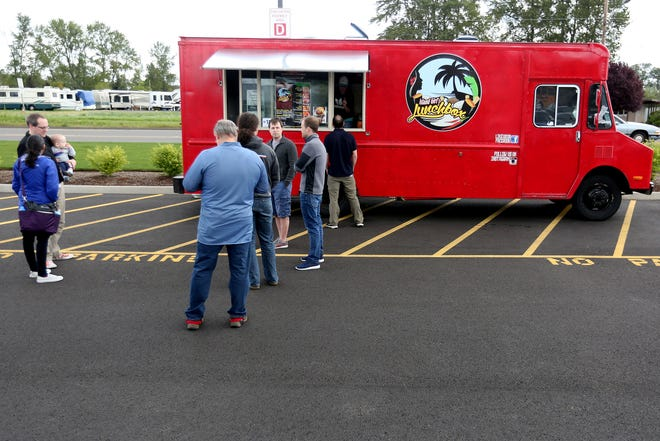 Customers line up for orders from the Island Girl's Lunchbox food truck in Salem, April 15, 2016.