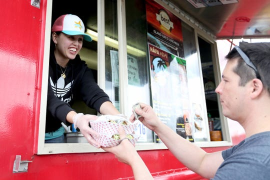 Stephanie Sosa serves Dustin Keller his bulgogi burritos from her food truck, Island Girl's Lunchbox, in Salem, April 15, 2016.