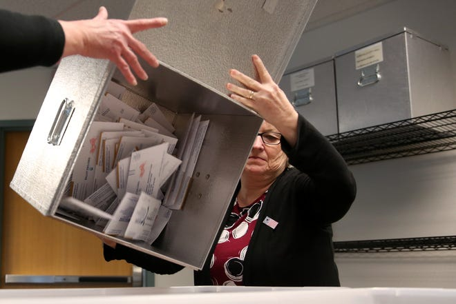 Patti Butler, a Marion County Elections employee, unloads a ballot box to sort envelopes at the Marion County Elections Office in Salem on Thursday, Oct. 25, 2018.