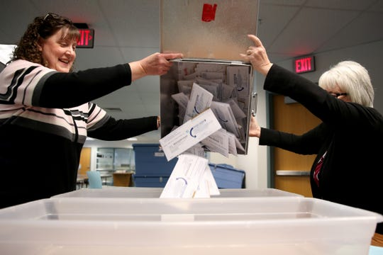 Beth Sorenson, left, and Patti Butler, Marion County Elections employees, unload a ballot box to sort envelopes at the Marion County Elections Office in Salem on Thursday, Oct. 25, 2018.