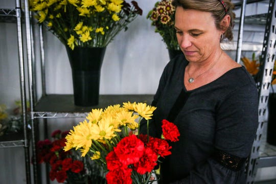 Christi Yancey picks flowers for an arrangement Tuesday, Oct. 23, 2018, at Friendly Flower Shop.
