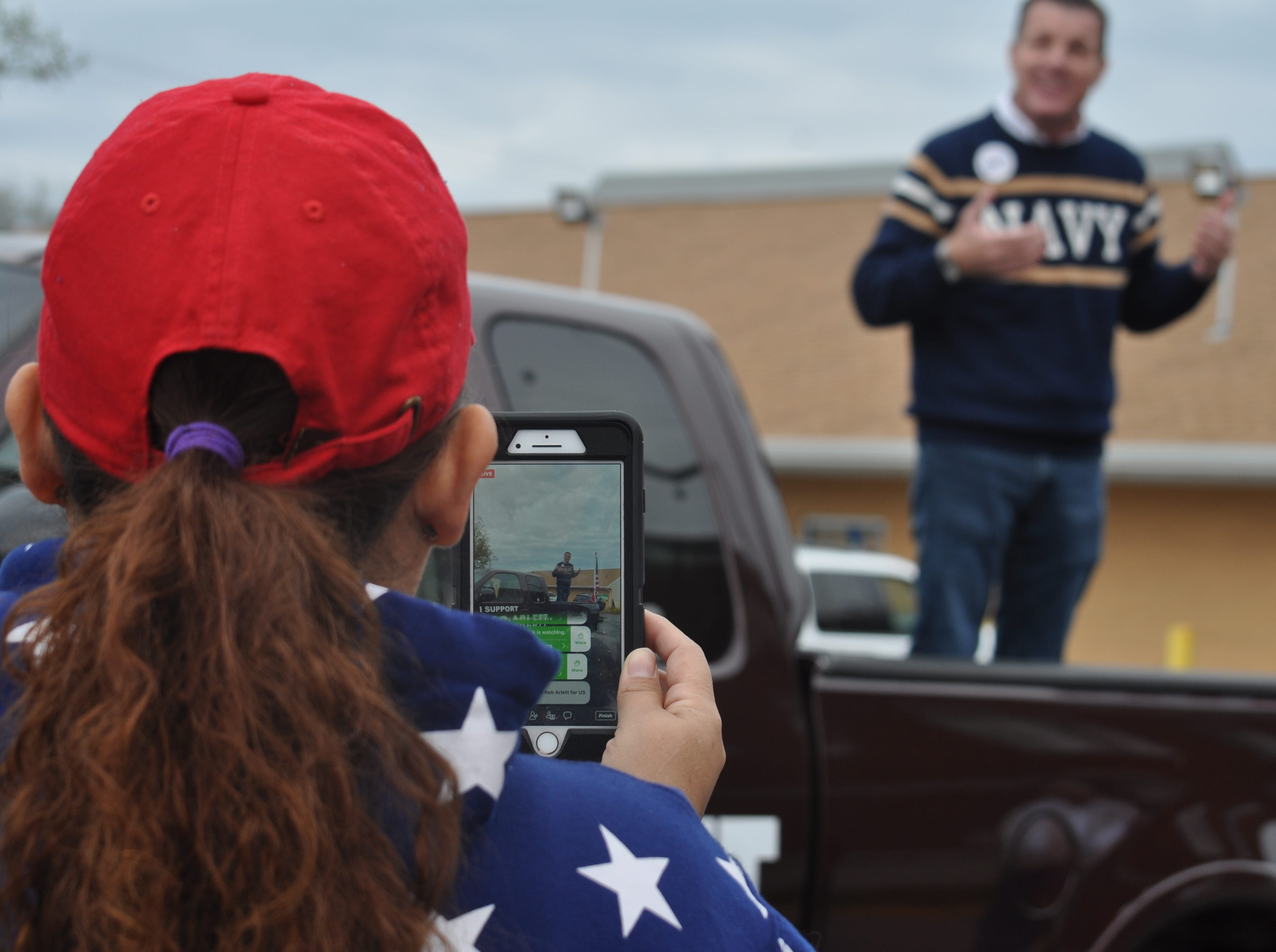 A supporter of U.S. Senate candidate Rob Arlett films his speech for Facebook Live on Oct. 20 in Millsboro.