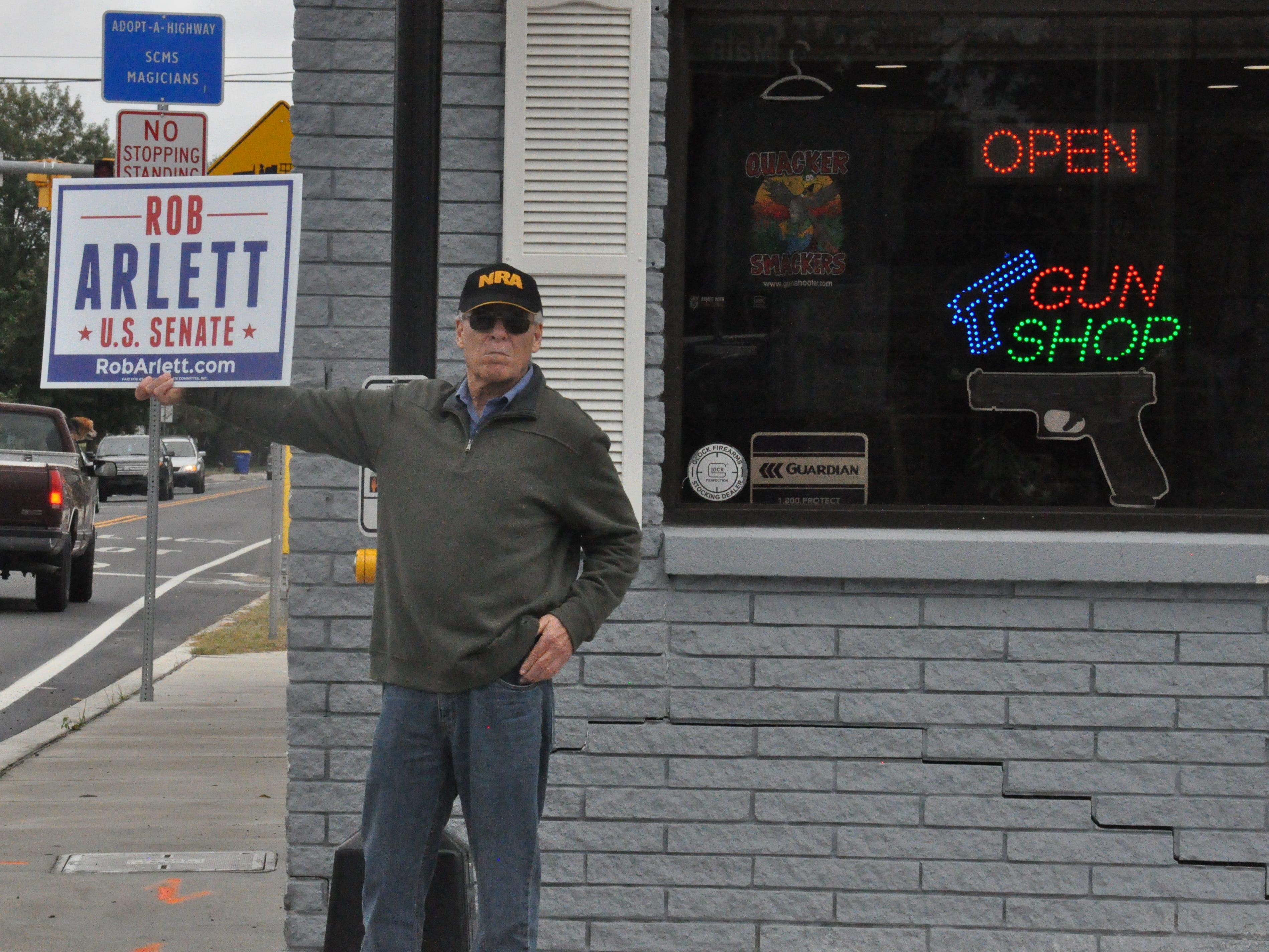 Retired civil service worker Thomas Fudge, 67, holds a sign for U.S. Senate candidate Rob Arlett on a street corner in Millsboro.