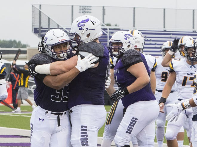 Gabe Watson (left) is hugged by teammates after scoring a touchdown in USF's win over Concordia-St. Paul