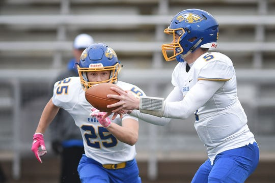 Aberdeen Central's Austin Huff (5) hands the ball off to 	Chris Weber (25) during the game against Roosevelt Thursday, Oct. 25, at Howard Wood Field in Sioux Falls.