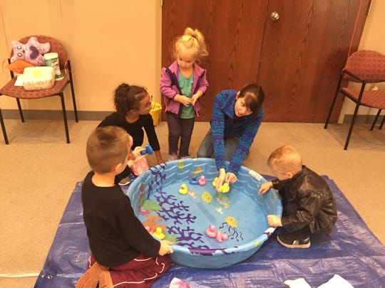 Kendra Hayes, a volunteer with Stars Kids Club, helps (from left) Jaxson Grant, 5, Allee Grant, 6, Trinity Gill, 2, and Callum Grant, 3, with the duckling game during the Stars Kids Club kickoff event Oct. 12. Cold and rainy weather forced the event inside, but there was no lack of entertainment for the kids.