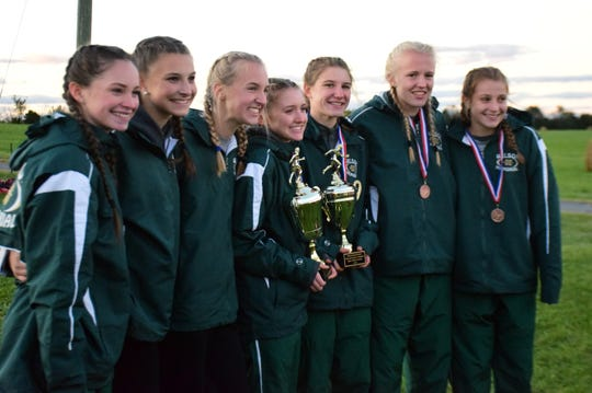 Wilson Memorial's girls team poses with the regular-season and meet championship trophies at the Shenandoah District Cross Country Championships on Wednesday, Oct. 24, 2018, at New Market Battlefield Park in New Market, Va.