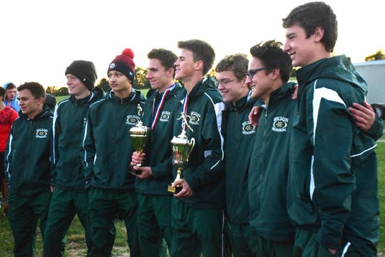 Wilson Memorial's boys team poses with the regular-season and meet championship trophies at the Shenandoah District Cross Country Championships on Wednesday, Oct. 24, 2018, at New Market Battlefield Park in New Market, Va.