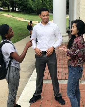 While speaking after class with TV 3 reporter Matt Fultz, MBU students Kristen Franklin and Vivian Ruiz make their points.