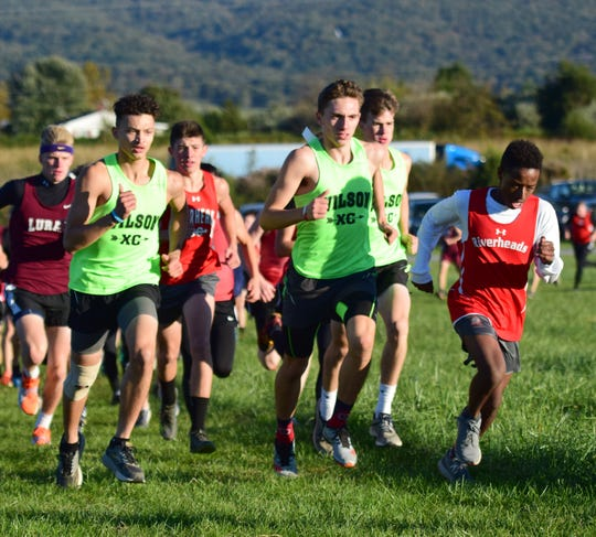 From left, Wilson Memorial's Taylor Armstrong and Vincent Leo, and Riverheads' Abenezer Knight compete in the opening stages of the boys race at the Shenandoah District Cross Country Championships on Wednesday, Oct. 24, 2018, at New Market Battlefield Park in New Market, Va.