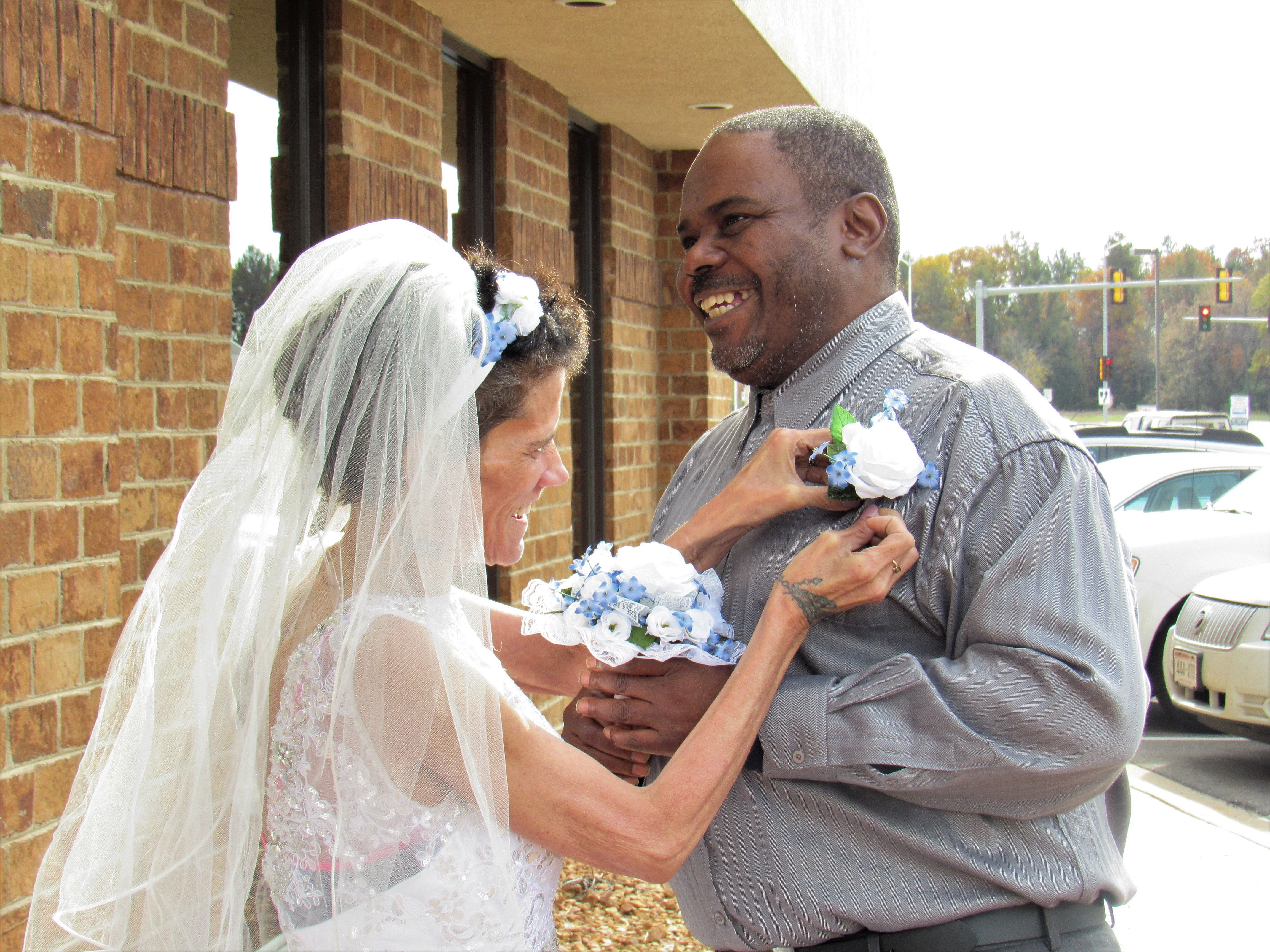 Lisa Fredrick adjusts Shawn Ivy's boutonniere after their wedding ceremony on Thursday, Oct. 25, 2018, outside the Ministry Home Care office in Plover.