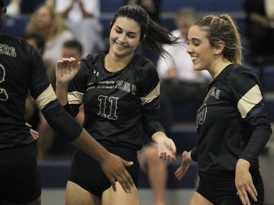 Nicole Cross (11) and Mary Claire Ricco (10) celebrate a point with their team as the St. John Paul II volleyball team won a 3-0 regional semifinal match against St. Johns Country Day.