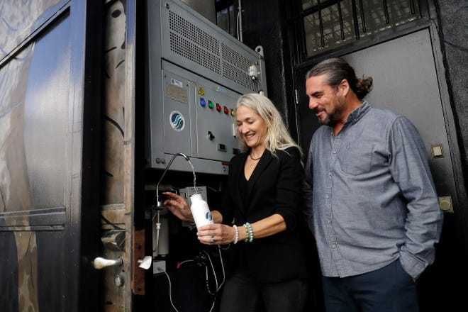 Skysource/Skywater Alliance co-founders David Hertz, right, and his wife, Laura Doss-Hertz, demonstrate how the Skywater 300 works in Los Angeles. The company received the $1.5 million XPrize For Water Abundance for developing the Skywater 300, a machine that makes water from air.