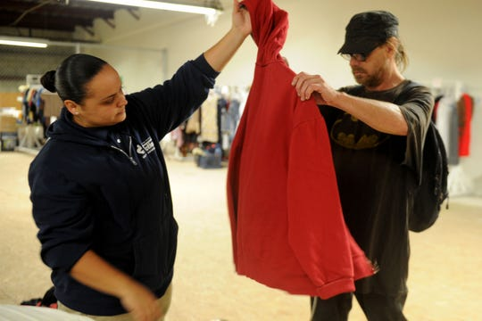 Ninna Castellano, the homeless services manager at Community Action in Oxnard, helps Stevo Zens with a sweatshirt and a pillow. The day center helps the homeless in Oxnard. The homeless can get snacks, use computers, do laundry,  get a haircut and other services at the center.