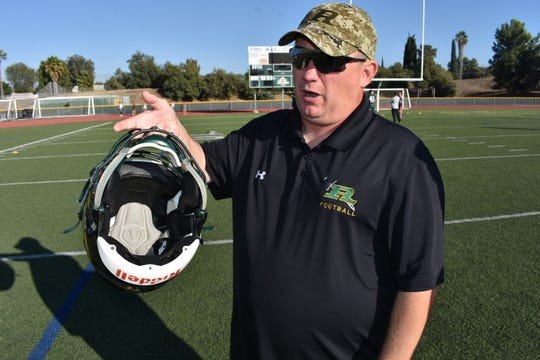Royal High School Coach Matt Lewis displays the Riddell helmets with a system called InSite that measures the impact of collisions.