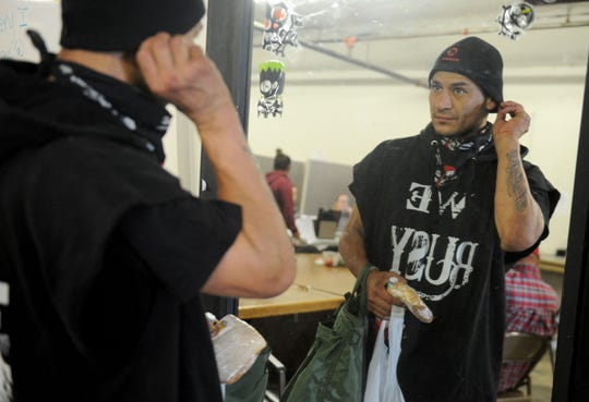 William Orante uses a mirror to fix himself up at Community Action in Oxnard. The center offers a variety of services to the homeless and plans to stay open even as plans move ahead on permanent shelters in both Oxnard and Ventura.