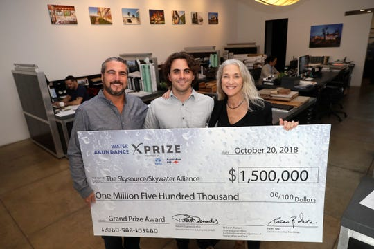 The Skysource/Skywater Alliance co-founders David Hertz, left; his wife, Laura Doss-Hertz, right; and project designer Willem Swart pose for a photo with an image of a $1.5 million prize the company received Wednesday in Los Angeles. The company received the $1.5 million XPrize For Water Abundance for developing the Skywater 300, a machine that makes water from air.