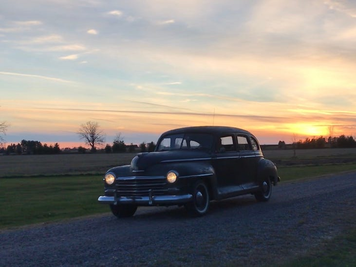 The '48 Plymouth cruises down a gravel lane near Arpin.