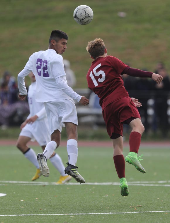 Ossining's Nolan Lenaghan (15) and New Rochelle's Steven Izazaga (22) battle for control of the ball during the Class AA boys soccer semifinal game at Ossining High School onOct. 24, 2018. Ossining defeats New Rochelle 2-0.