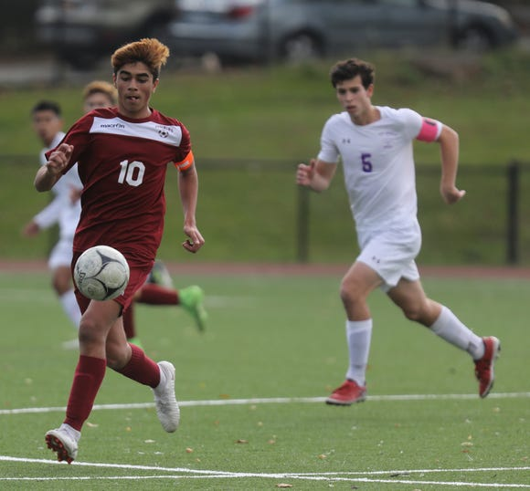Ossining's Alessio Hernandez (10) keeps the ball away from New Rochelle's David Benko (5) during the Class AA boys soccer semifinal game at Ossining High School onOct. 24, 2018. Ossining defeats New Rochelle 2-0.