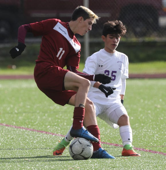 Ossining's Mateo Marra (11) and New Rochelle's Jordan Reyes (25) battle for control of the ball during the Class AA boys soccer semifinal game at Ossining High School onOct. 24, 2018. Ossining defeats New Rochelle 2-0.