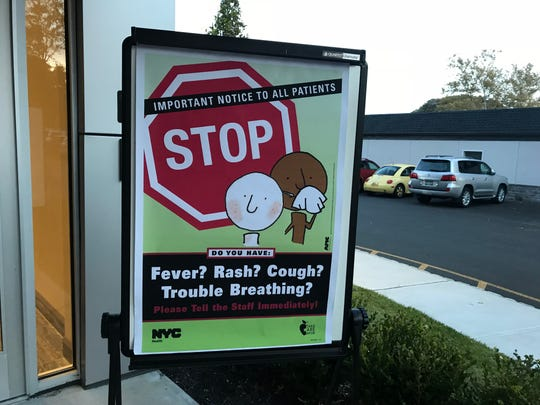 A free measles vaccine clinic Nov. 2, 2018, in Monsey, New York, posted signs for those taking advantage of the shots to tell staff about symptoms of any illness because they could infect others.
