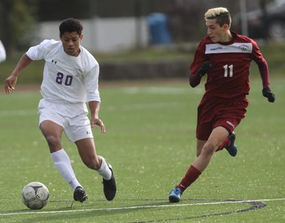 Ossining's Mateo Marra (11) and New Rochelle's Aaron Blake (20) battle for control of the ball during the Class AA boys soccer semifinal game at Ossining High School onOct. 24, 2018. Ossining defeats New Rochelle 2-0.
