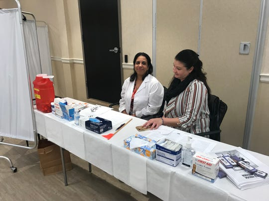 Sheela Geevarghese (l) and Xiomara Lopez with the Rockland County Department of Health's measles, mumps, and rubella (MMR) vaccines at the free clinic in Monsey on Thursday.