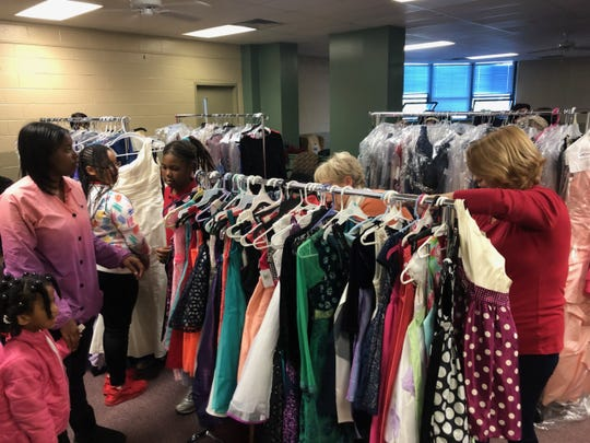 Young girls pick out their outfits for the Police and Princess Ball Wednesday evening. Donated dresses poured in from the community, totaling four racks of colorful gowns.
