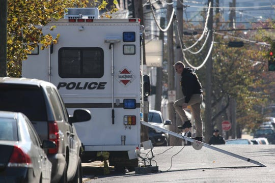 A police officer investigating a suspicious package at the Lancaster Avenue post office on Thursday morning walks back into an emergency vehicle.