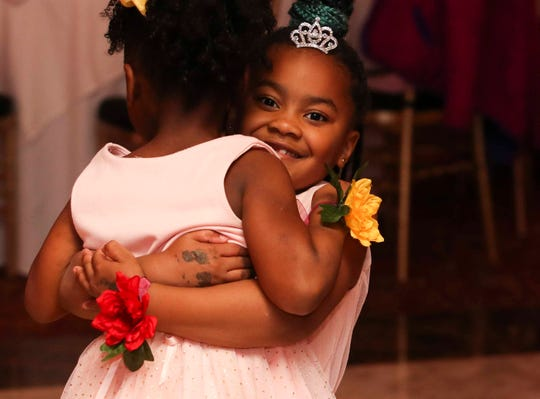 Riley hugs a fellow attendee on the dance floor as young girls are treated to a Police and Princess Ball at the Waterfall banquet center in Claymont Wednesday. The event, spearheaded by New Castle County Police but with involvement from other departments and businesses, brought dozens of girls to the dance for a positive experience with police.