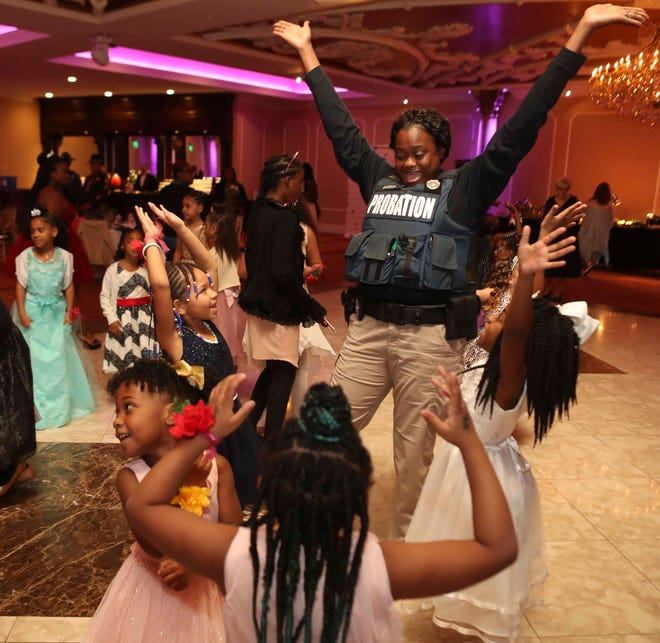 Probation officer Samaria Pfleegor dances with attendees as young girls are treated to a Police and Princess Ball at the Waterfall banquet center in Claymont Wednesday. The event, spearheaded by New Castle County Police but with involvement from other departments and businesses, brought dozens of girls to the dance for a positive experience with police.