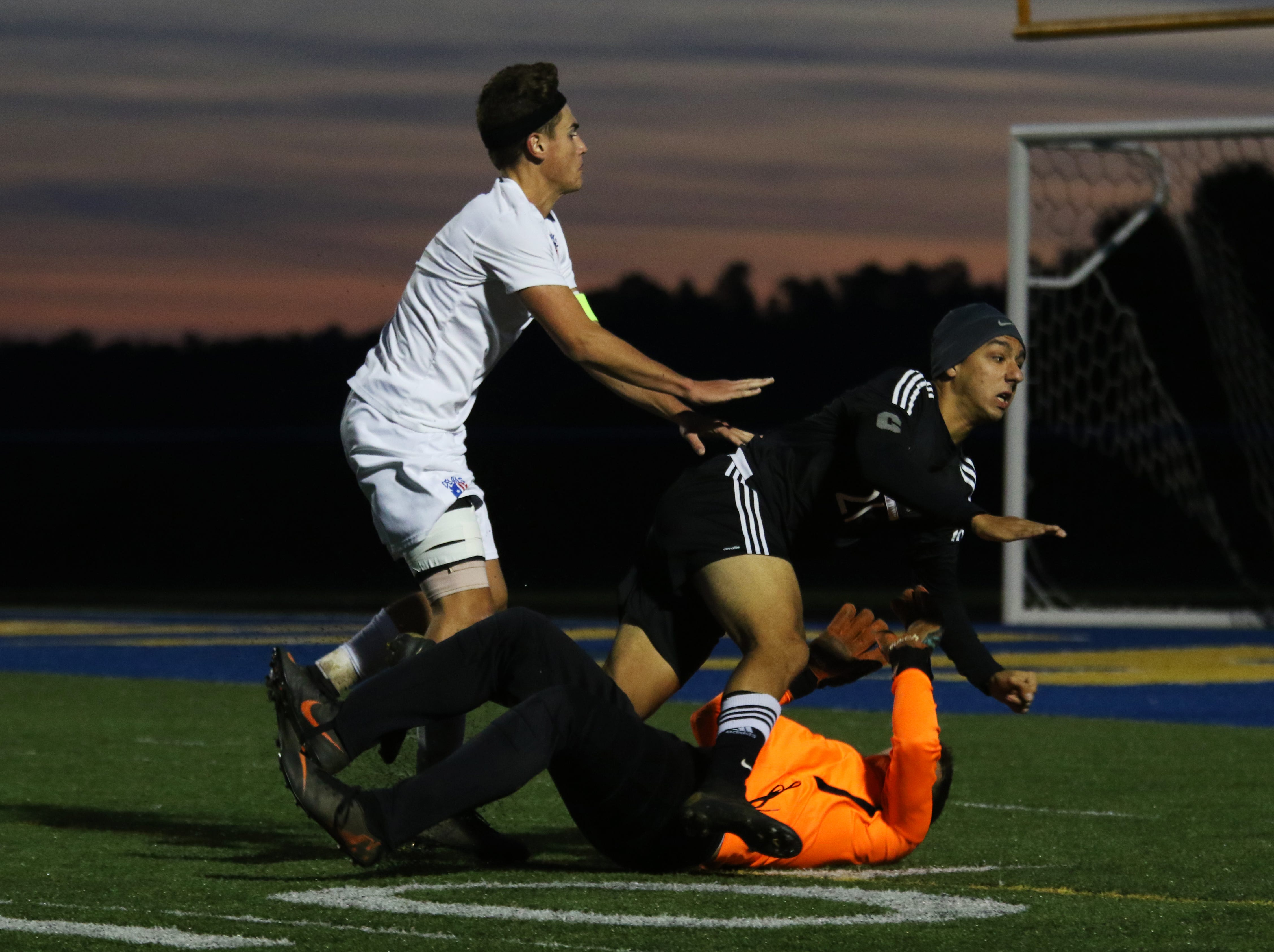 River View's Kyle Moses collides with keeper Hunter Haines while chasing a ball from Zanesville's Jack Thorne. River View knocked Zanesville out of the tournament with a 2-0 win over the Blue Devils Wednesday night at Maysville High School.