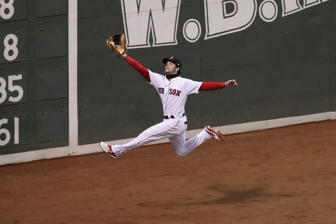 Game 2 at Fenway Park: Red Sox left fielder Andrew Benintendi makes a leaping catch in the fifth inning.