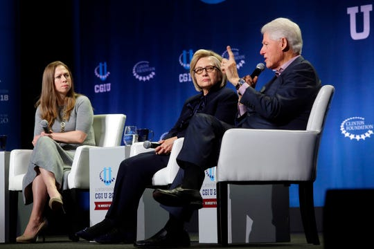 Chelsea Clinton, left; and her mother, former Secretary of State Hillary Clinton, listen as former President Bill Clinton, Chelsea Clinton's father, speaks Oct. 16, 2018, during the annual Clinton Global Initiative conference at the University of Chicago.