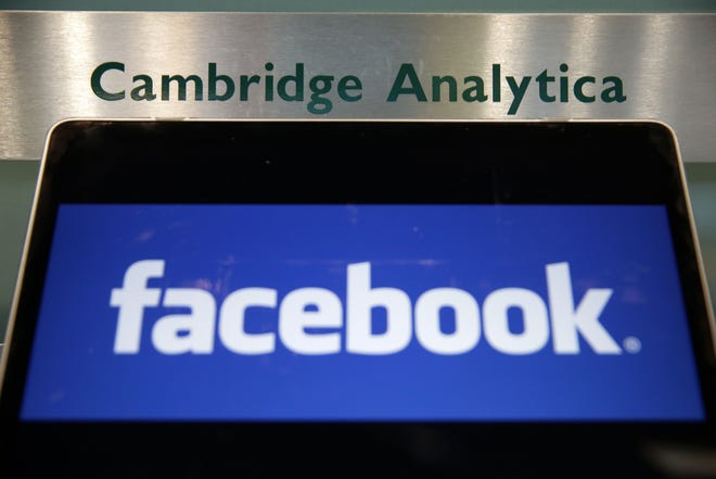 In this file photo taken on March 21, 2018 A laptop showing the Facebook logo is held alongside a Cambridge Analytica sign at the entrance to the building housing the offices of Cambridge Analytica, in central London.