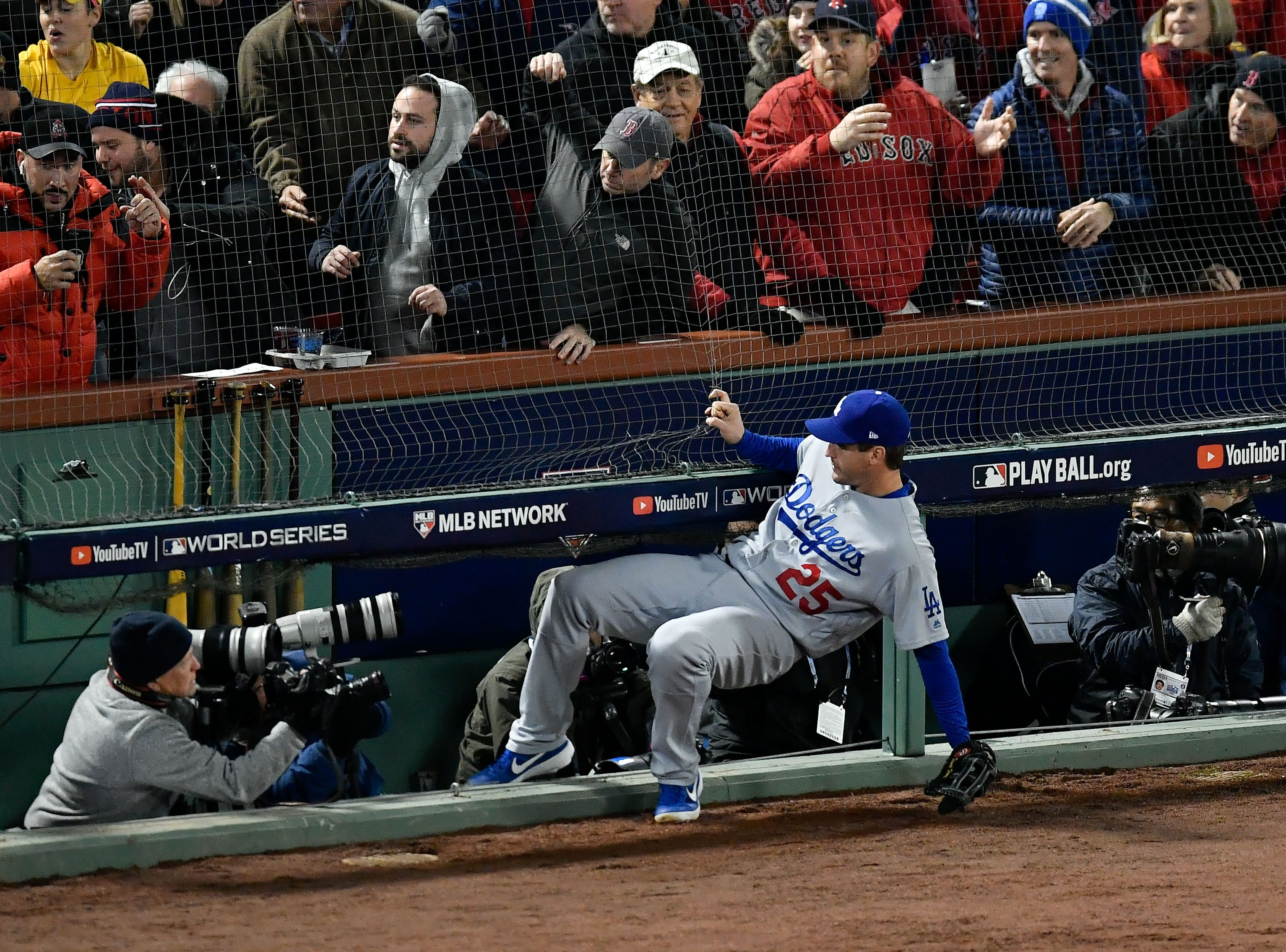 Game 2 at Fenway Park: Dodgers first baseman David Freese falls into the photographer pit while attempting to field a foul ball in the second inning.