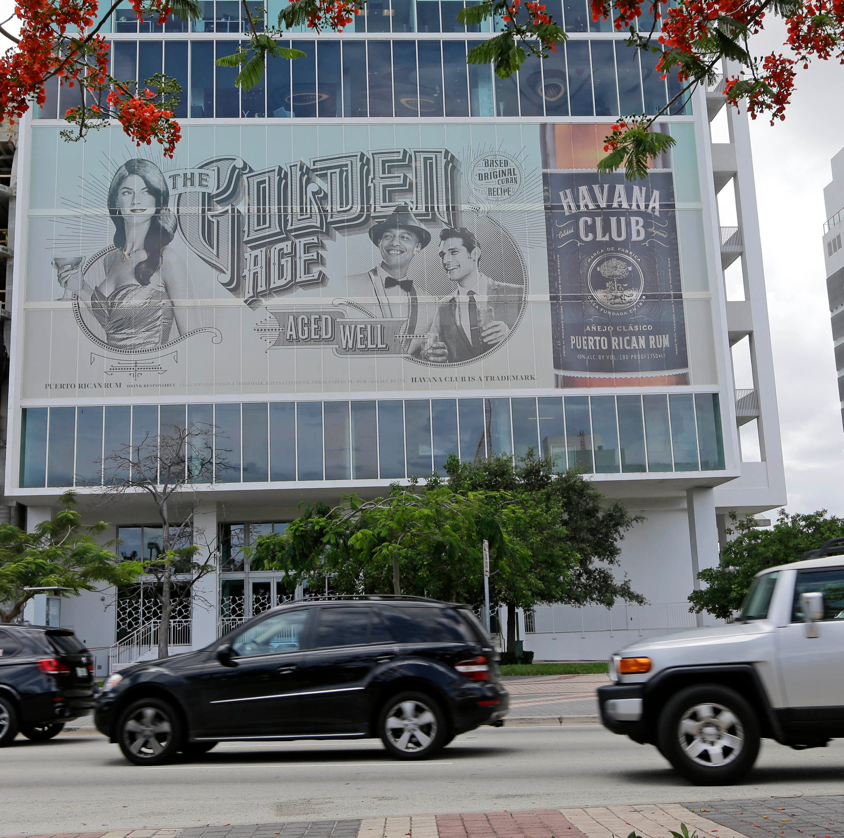 In this photo taken Tuesday, June 7, 2016, cars drive by a Havana Club billboard on Biscayne Boulevard in downtown Miami.