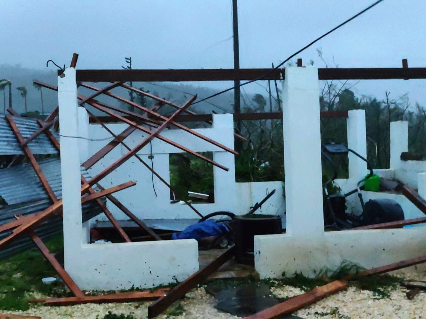 In this photo provided by Glen Hunter, damage from Super Typhoon Yutu is shown outside Hunter's home in Saipan, Commonwealth of the Northern Mariana Islands, Thursday Oct. 25, 2018. As the powerful storm crossed over the island the walls shook in Hunter's concrete home, a tin roof over the garage blew away and howling winds terrified his cats. Maximum sustained winds of 180 mph (290 kph) were recorded around the eye of the storm, which passed over Tinian and Saipan early Thursday local time, the National Weather Service said.