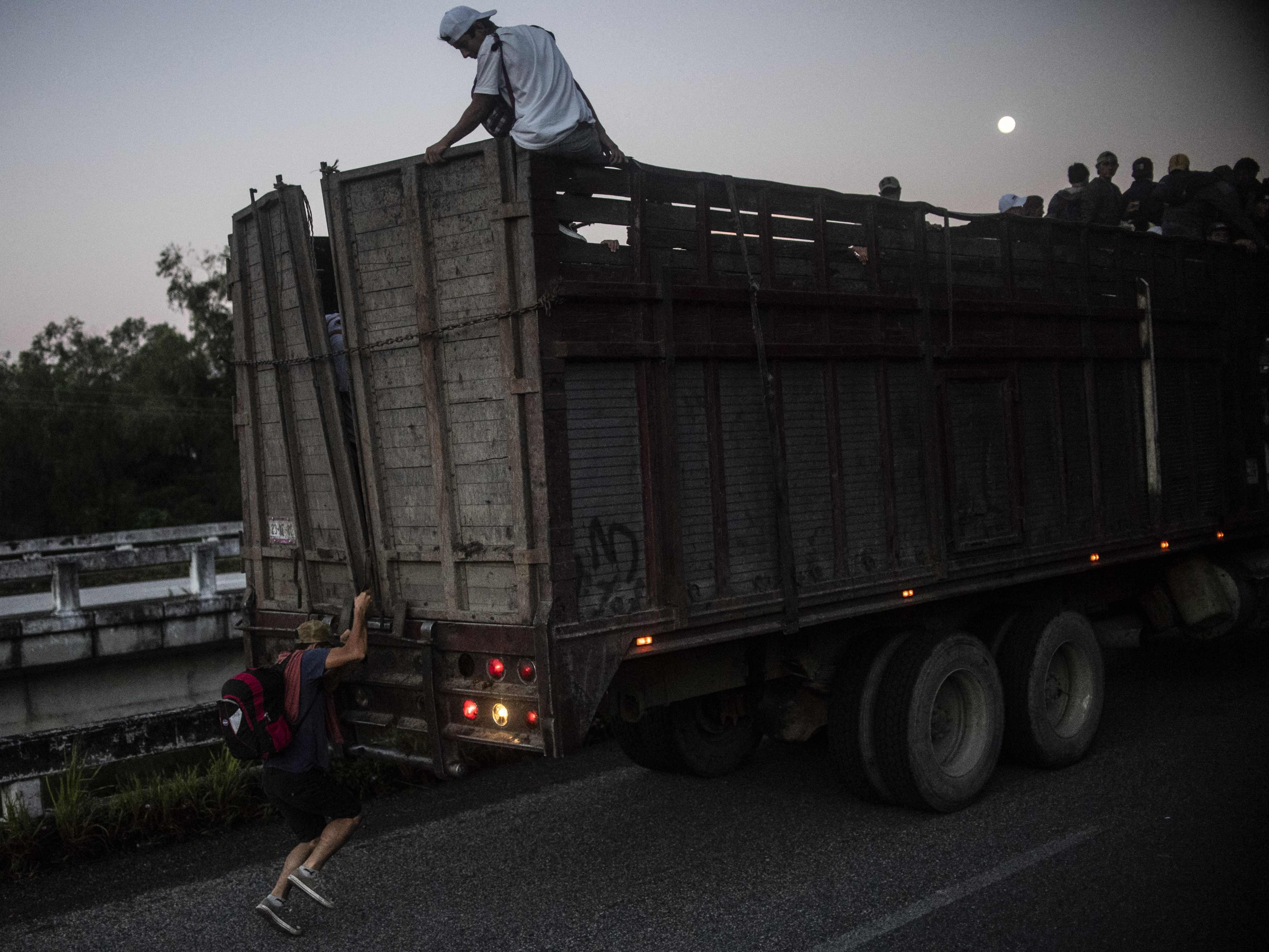 Central American migrants climb into a truck during a caravan to the U.S., near Mapastepec, Chiapas state, Mexico, Oct. 25, 2018.