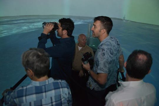 """Gerard Butler peers into the binoculars, but it was director Donovan Marsh (center right) who saw a vision for the film's set aboard the USS Houston before shooting began on """"Hunter Killer."""""""